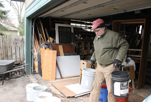 Joe Knaeble sifts debris out of hundreds of pounds of salt at his garage in The Wedge. Photo by Michelle Bruch