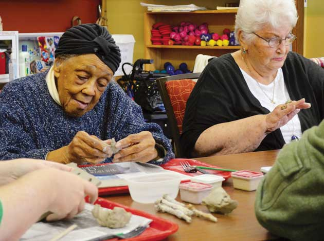 Ponese Skinner (left) and Lois Belmore make clay plaques as part of a workshop in the Southwest Senior Center's DayElders program. Photo by Nate Gotlieb