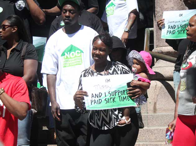 A woman rallied with her baby Wednesday afternoon on the steps of City Hall for a new paid sick time ordinance. Photo by Sarah McKenzie