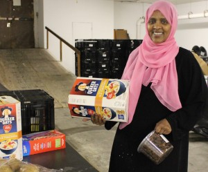 Fartun Weli is distributing dates and oatmeal at the nonprofit Isuroon's new food shelf on Nicollet. Photo by Michelle Bruch