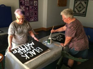 Sandy McDonald (l) and Betty Tisel make lawn signs in support of Black Lives Matter. Photo by Sarah Farley