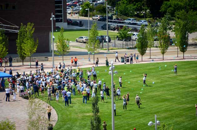 A large crowd takes part in a ceremonial Frisbee toss during the grand opening celebration for the new Commons park. Photo by Sarah McKenzie