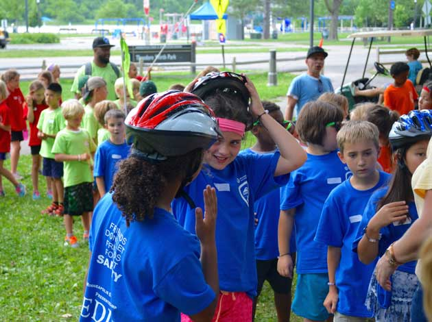 Youngsters at Minneapolis Safety Camp receive bicycle helmets courtesy of People for Parks, a nonprofit dedicated to improving and enhancing Minneapolis parks, on Aug. 1 at Theodore Wirth Park. The organization supplied 200 helmets for campers. Photo by Nate Gotlieb