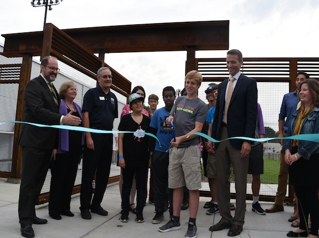 Peter Biros, a sophomore at Edison, cuts the ribbon, flanked by classmates and community leaders involved in the green campus project. Photo by James Healy.
