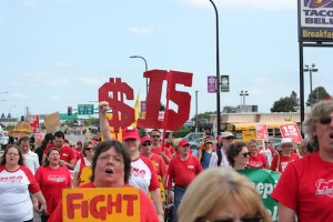 Striking Allina nurses joined $15 minimum wage supporters in a rally and march down West Broadway Avenue on Sept. 12. Photo by Dylan Thomas