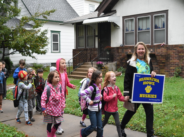 Deb Regnier, the principal of Hiawatha Community School, holds hands with Harper Thompson, 6, on International Walk and Bike  to School Day. Photo by Zoë Peterson.