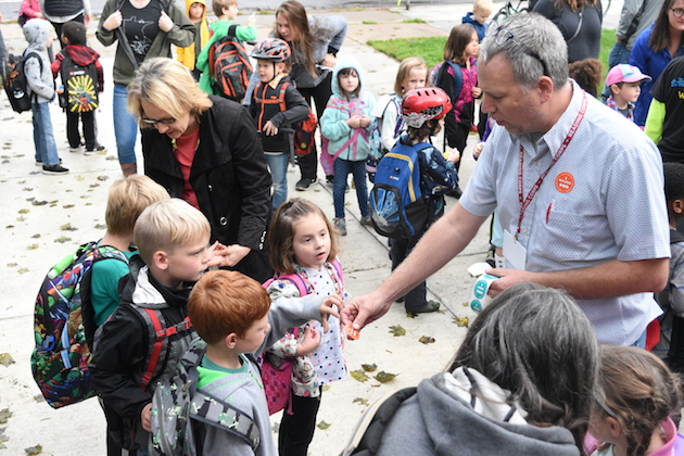 "Staff hands out ""I WALKED"" and ""I BIKED"" stickers to students who participated in the international celebration of getting to school on two feet or two wheels. Photo by Zoë Peterson."