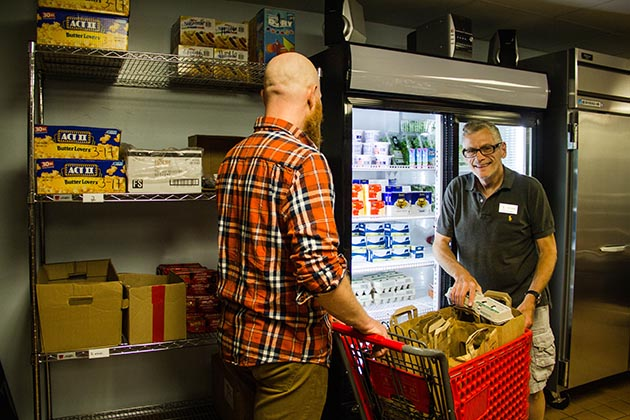 Food Shelf Manager Dan Capelli helps members select nutritious grocery options from the Food Shelf once a month. Each member is allowed 60 pounds of food per visit. Photo by Abraham Saraya