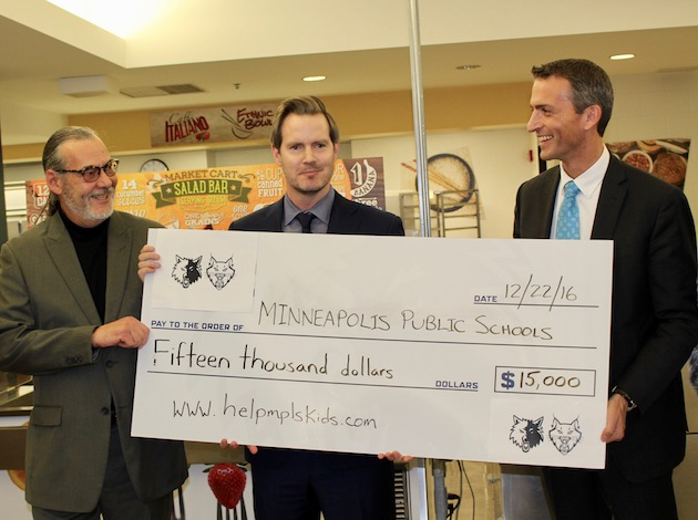 Minnesota Timberwolves CEO Ethan Casson (center) presents a $15,000 check to pay off overdue Minneapolis Public Schools lunch accounts. Supt. Ed Graff (right)  and Director of Culinary and Wellness Services Bertrand Weber (left) are also pictured. Photo by Nate Gotlieb