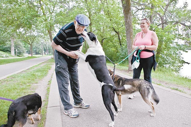 Bill Brice greeting a dog on the paths around Lake Harriet in 2010. File photo