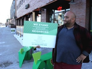 Rico Morales holds a new yard sign that promotes a welcoming environment in Kingfield. Photo by Michelle Bruch