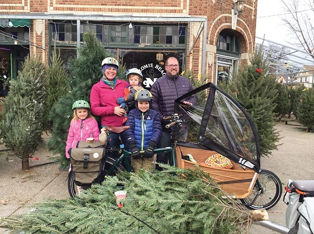 The Nafziger kids — Linus, 10, Freya, 8, and Arne, 2 — pile onto their family's bike trailer while dad, Adam, pedals and mom, Nicole, hitches a ride. It's just another everyday bike trip for this south Minneapolis family. Photo courtesy of Adam and Nicole Nafziger.