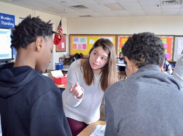 University of Minnesota freshman Hannah Manley works with Ramsey Middle School students in a math class on Feb. 10. Photo by Nate Gotlieb
