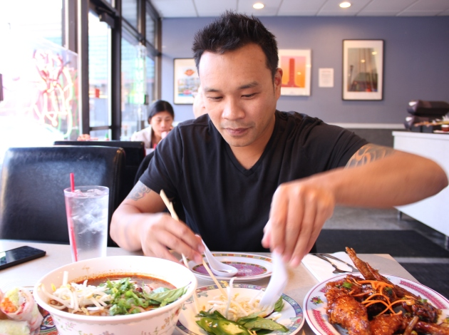 Yoom Nguyen adds bean sprouts, herbs and lime to the bun bo hue soup.