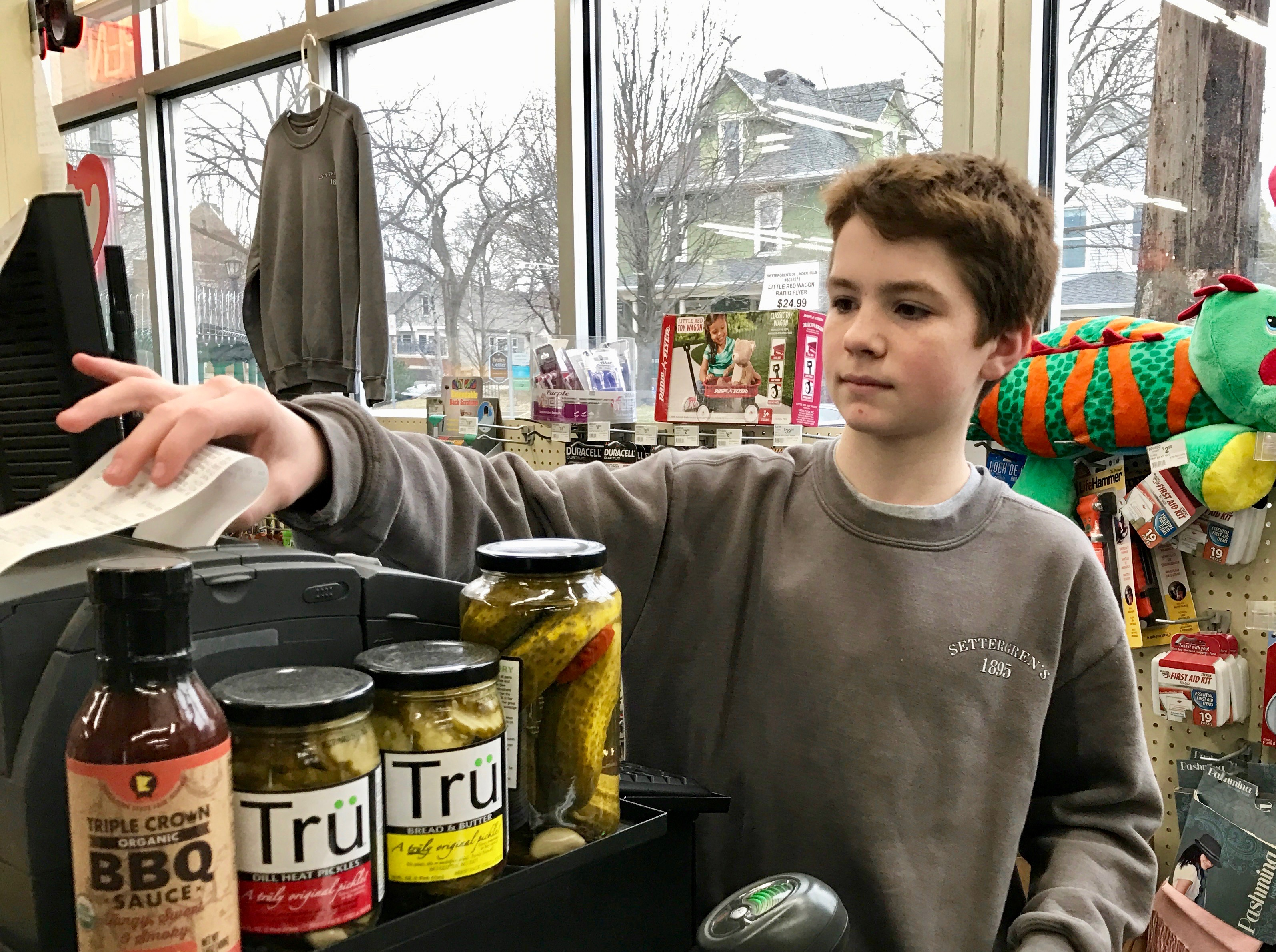 Fifteen-year-old Will Berlin works the cash register at Settergren Ace Hardware in Linden Hills. Businesses in Minneapolis are mulling over how a $15 minimum wage would affect their ability to hire youth workers. Photo by Nate Gotlieb