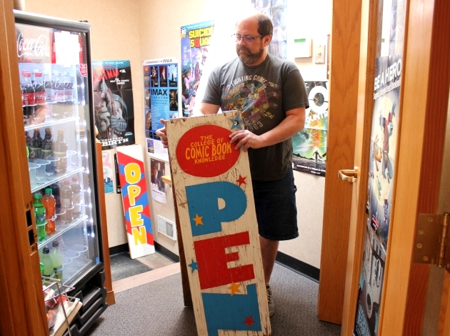 Tim Lohn pulls out a weathered sandwich board sign at Comic Book College, open since 1974 at 32nd & Hennepin.