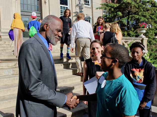 Ex-Minnesota Supreme Court Justice and Minnesota Vikings Hall of Fame football player Alan Page shakes hands with students outside of Justice Page Middle School on June 14. Photo by Nate Gotlieb