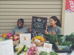 Barbara Fuller (left) and University of St. Thomas student Jadea Conway work at a farm stand operated by BrightSide Produce, a University of St. Thomas-based social enterprise. Photo courtesy BrightSide Produce
