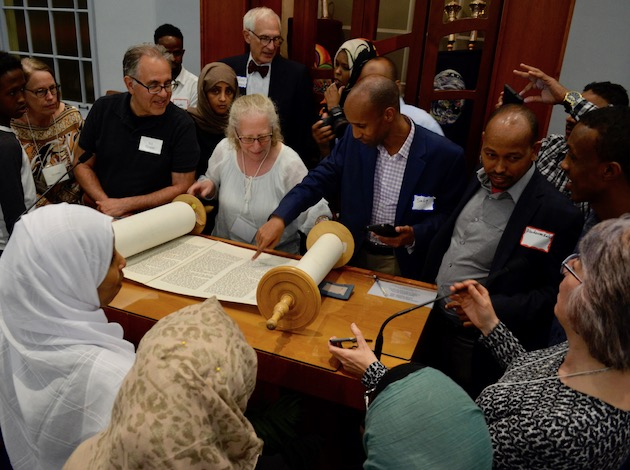 Shir Tikvah and Islamic Civic Society of America/Dar Al-Hijrah mosque congregants look at the Jewish holy scripture, called the Torah, after a post-sunset Ramadan dinner on June 7.