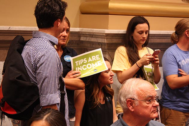 Tip credit advocates held signs during a June 22 public hearing on the municipal minimum wage ordinance. Photo by Dylan Thomas