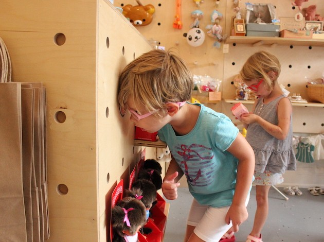Ingrid Johnson (l) peers through a peephole while Francine plays at Kinoko Kids.