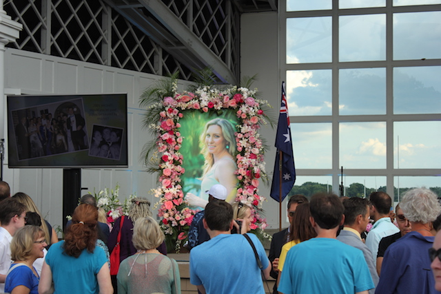A photo of Justine Damond next to an Australian flag on the state of the Lake Harriet Bandshell, where hundreds gathered Friday to remember the woman shot and killed by police in July. Photo by Dylan Thomas
