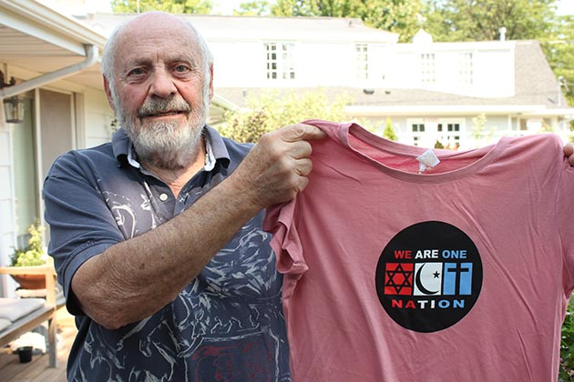 Bob Wolk holds one of the T-shirts he designed with his son, Seth. Photo by Dylan Thomas