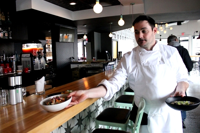 Chef Chris Gerster carries out bowls of raw salad and smoked grits at Hasty Tasty.
