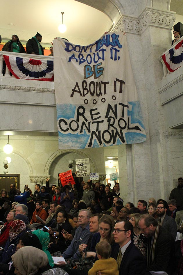Activists calling for rent control unfurled a banner from a second-floor balcony in the City Hall rotunda. Photo by Dylan Thomas