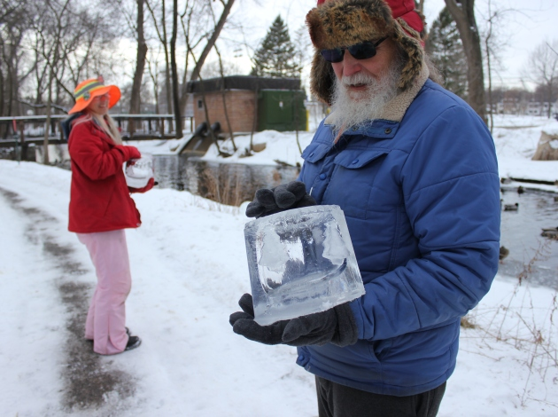 Mary Arneson and Dale Hammerschmidt place ice lanterns along Minnehaha Creek.