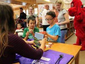 Students at Hmong International Academy get stickers to put on their new books during a book fair on May 22.