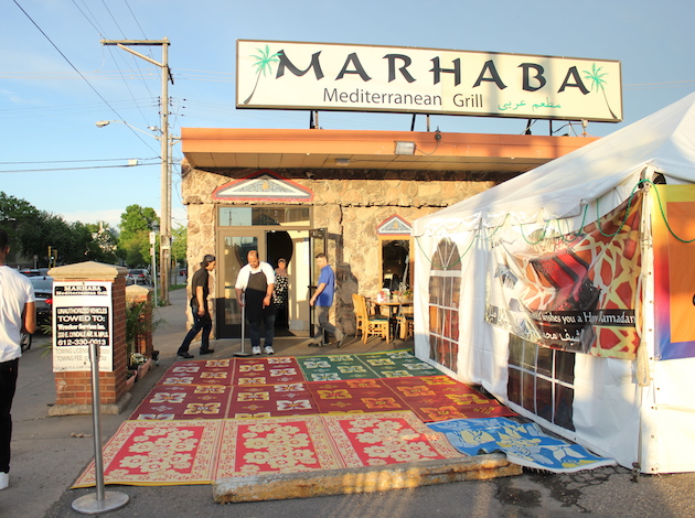Marhaba Grill owner Mohamed Shehata (center) prepares for an iftar dinner in late May.