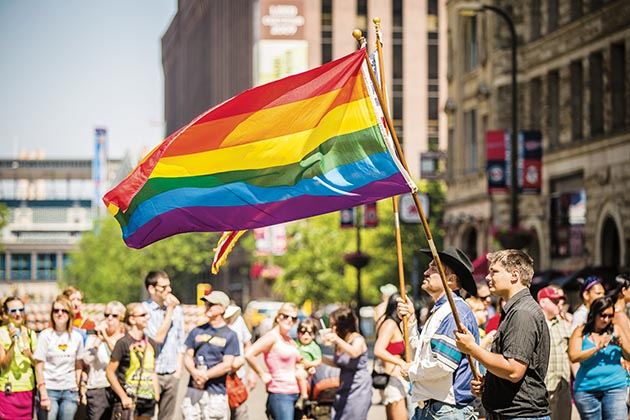 Marchers in the 2013 Twin Cities Pride parade carry rainbow flags as spectators watch along Hennepin Avenue. File photo