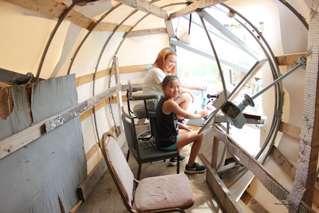 Kaia (l) and Olivia sit in the control room of the homemade Millennium Falcon at Adventure Playground.