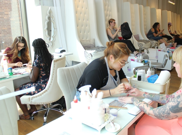 Little Luxuries Nail Lounge owner Amy Vang (at left) and sister Melody Vue (center) provide nail services.