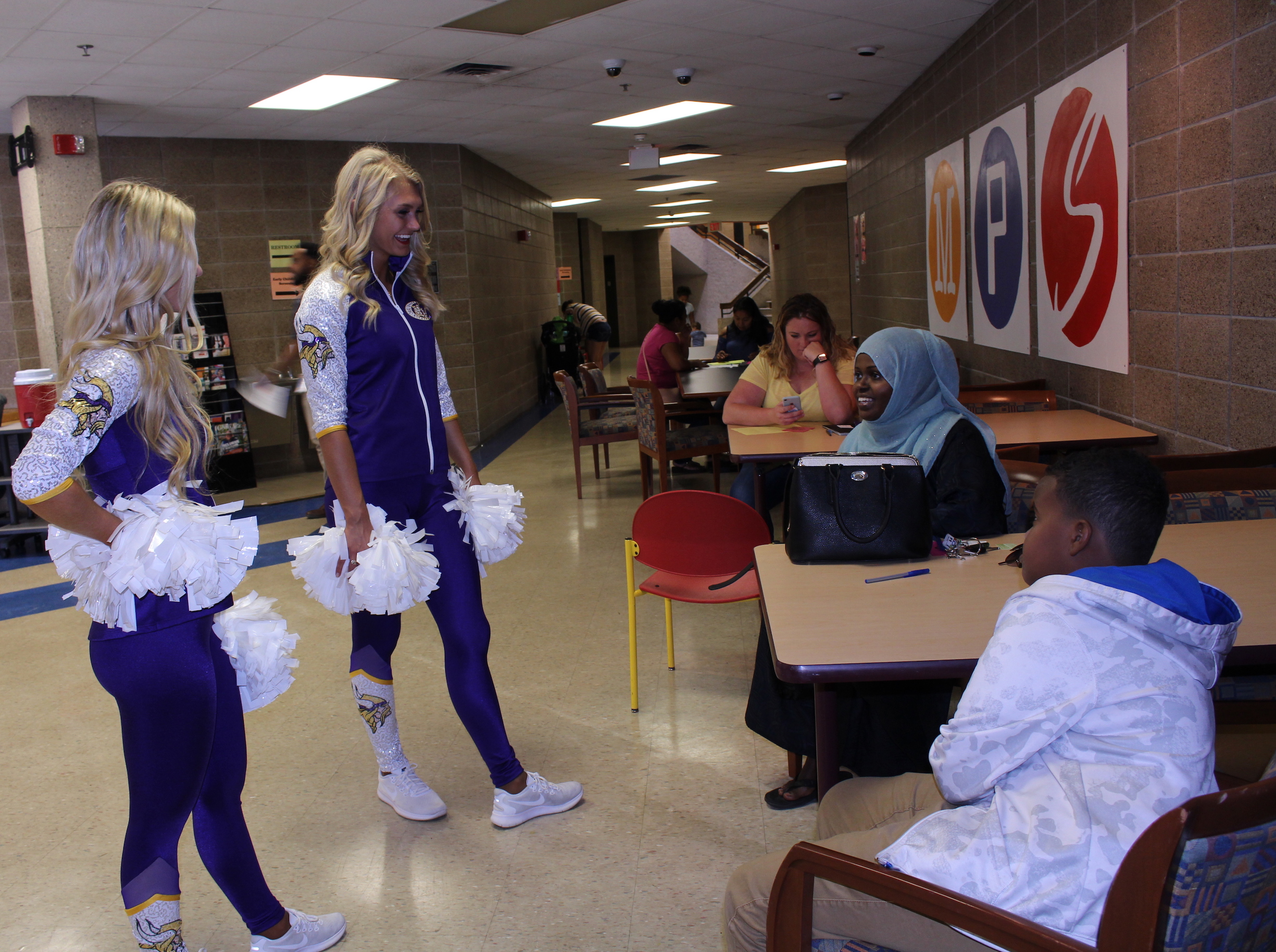 Minnesota Vikings cheerleaders Leah (center) and Meghan (left) talk with Fawsiya Maow and her son Ismail Abdulqadir at the Minneapolis Public Schools' New Families Center on Wednesday.