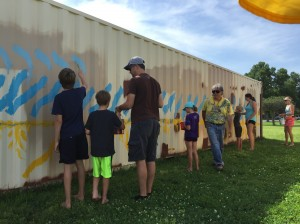 The Hale-Page-Diamond Lake Community Association recently teamed up with artist Jimmy Longoria (center right) to paint a pair of cargo boxes at Todd Park. Photo courtesy Sarah Sillers