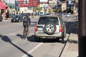 A cyclist rides around a car parked in the Hennepin Avenue bicycle lane between 11th and 12th streets. When approached for an interview, the car's driver pulled away. Photo by Dylan Thomas