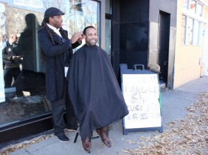 Upper Cuts Barber Shop owner Monell Castellan (l) cuts Brian Moore's hair outside his former storefront on Nicollet.