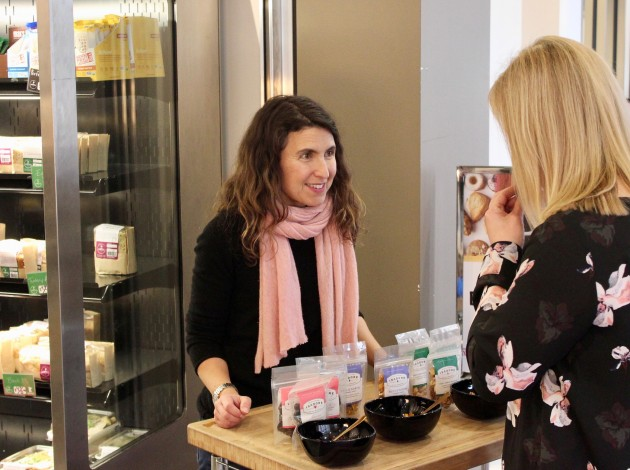 Isadore Nut Co. founder Tasya Kelen offers a sample to a woman in the Minneapolis Skyway. Photo by Andrew Hazzard.