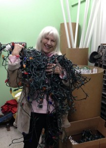 Sue Welna of the Welna Ace Hardware stores hoists an armload of holiday light strands bound for the recycler. Photo by Mira Klein