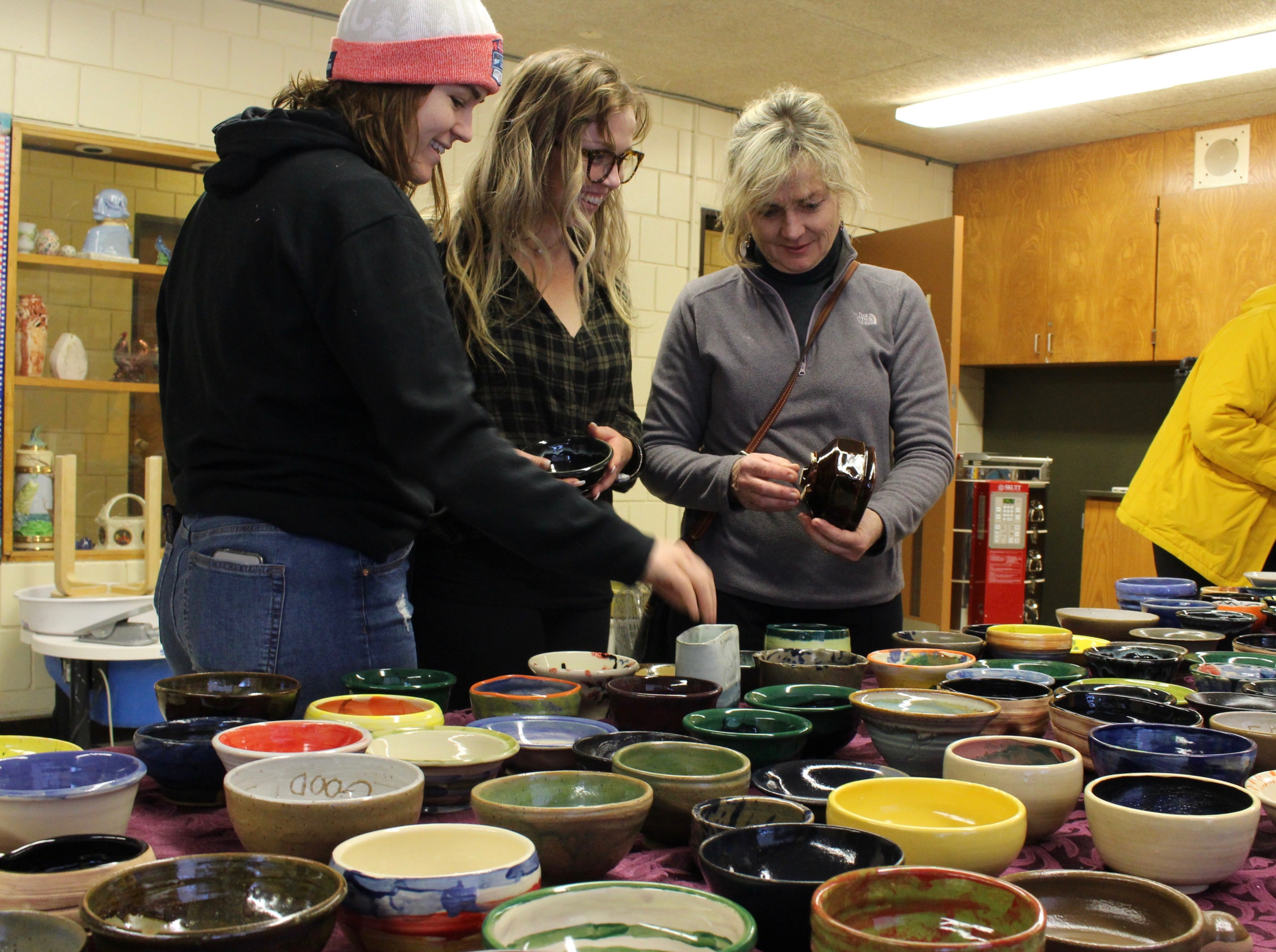 Ivy, Robin and Judith Forbes pick out bowls Thursday at the Kingfield Empty Bowls event. Photo by Nate Gotlieb