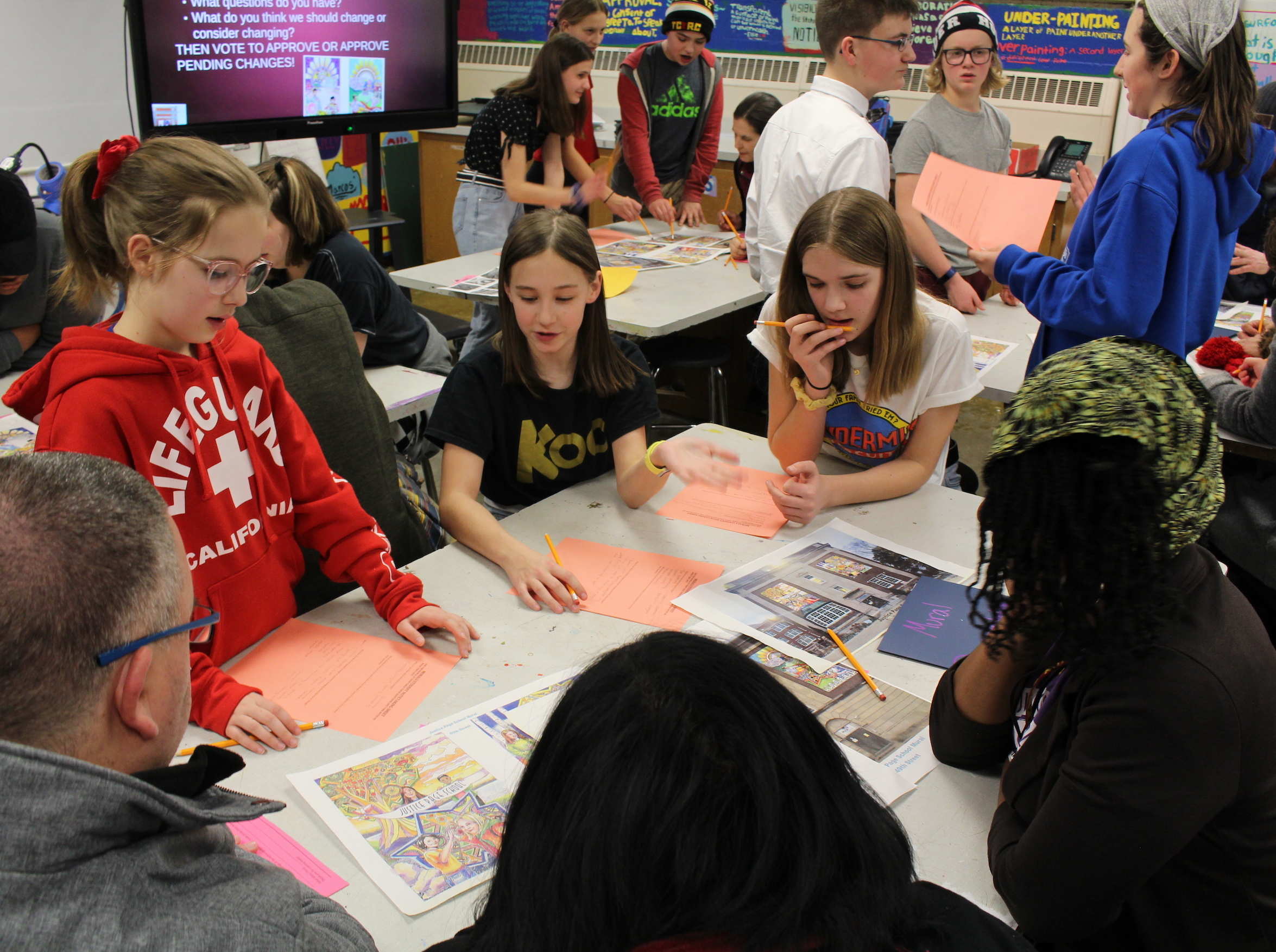Students in a Justice Page Middle School art class gather feedback on designs for murals that will hang outside the school. Photo by Nate Gotlieb