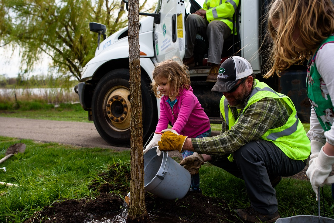 A MPRB arborist helps a child plant a tree at a previous Arbor Day celebration. This year's city celebration will take place at Theodore Wirth Regional Park on April 26. Photo courtesy of the Minneapolis Park and Recreation Board.