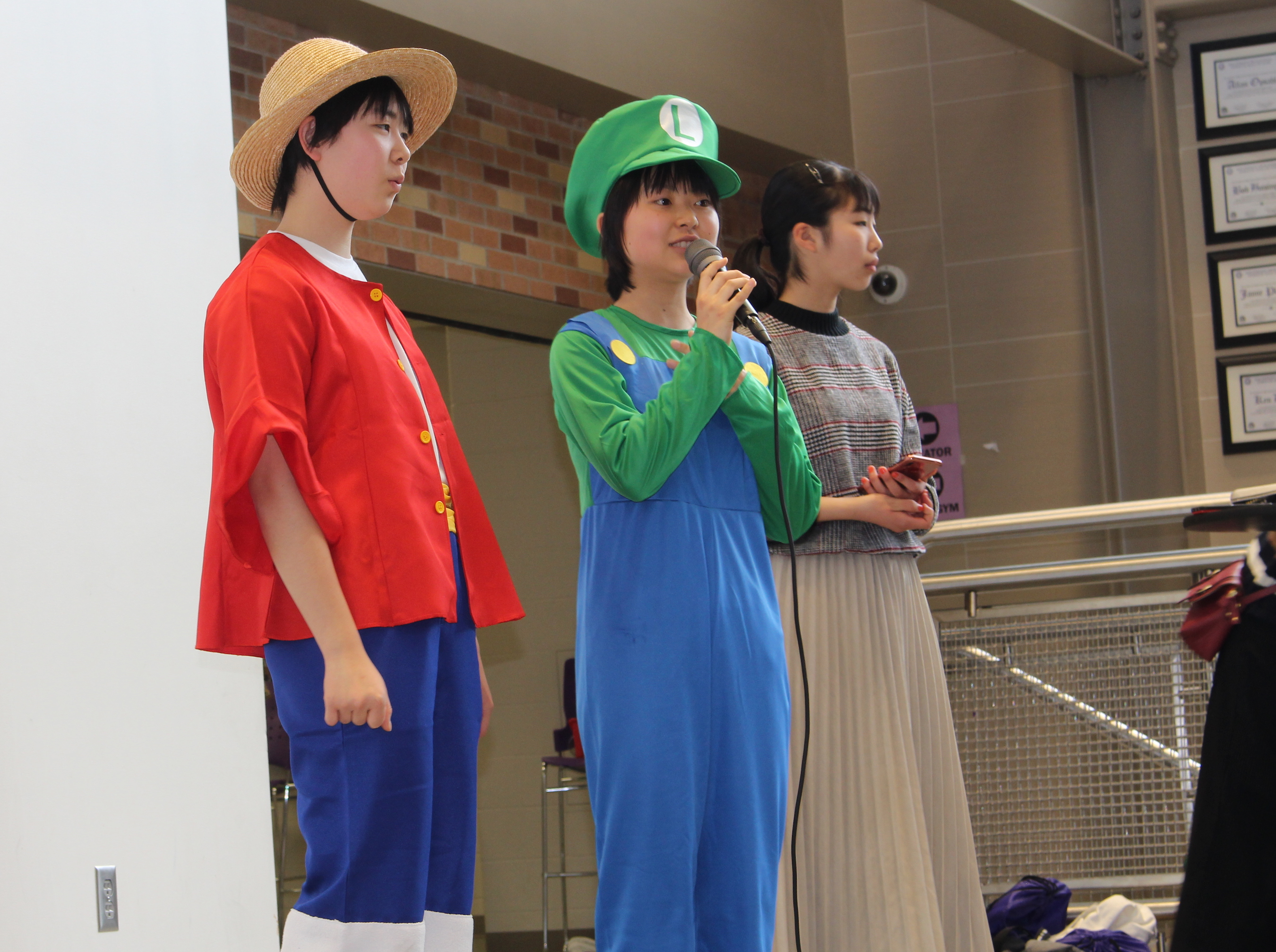 Students Honoka Yamamoto (left) and Himeka Miyoshi (center), of Kasugaoka High School in Osaka, Japan, perform in a skit March 1 at Southwest High School. Photo by Nate Gotlieb