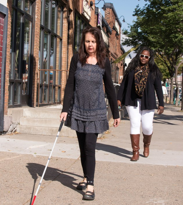 A Vision Loss Resources client learns safe travel skills with an instructor on Lyndale Avenue. Photo by Bruce Silcox