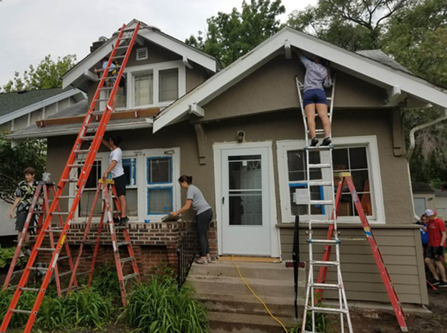 "Volunteers and staff from Habitat for Humanity's ""Brush with Kindness"" program repair and paint the exterior of a South Minneapolis home. The work was done in coordination with a Minneapolis program that helps homeowners unable to comply with city housing regulations. Image courtesy of Twin Cities Habitat for Humanity"