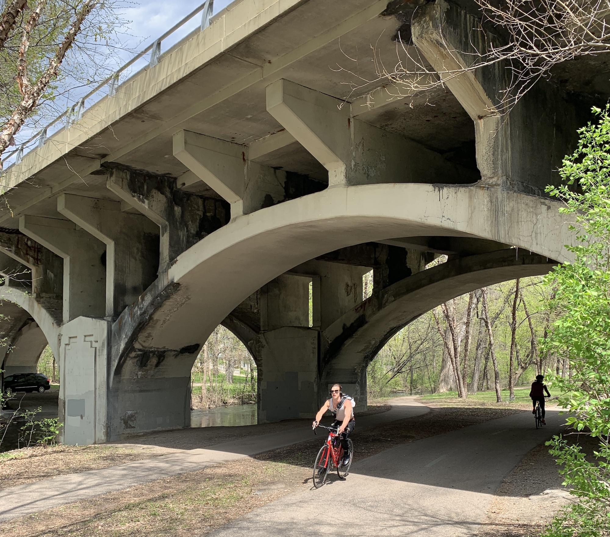 A biker travels under the Nicollet Avenue bridge along Minnehaha Creek