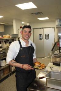 Chef and owner Alejandro Castillon Prieto stands with a freshly made burger in the kitchen of his new restaurant, Prieto, at the corner of Lake & Lyndale. Photo by Andrew Hazzard