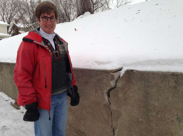 Elizabeth Howell next to the cracked retaining wall near her home, which has been at the center of an ongoing dispute she has had with the city over who is responsible for paying for repairs. Credit: